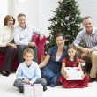 Family sitting by christmas tree — Stock Photo