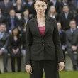 Business woman standing in front of people — Stock Photo