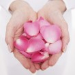 Woman cupping hands full of petals — Stock Photo #33837959