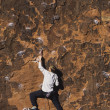 Stock Photo: Rock climber climbing cliff