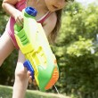 Little girl shooting water pistol — Stock Photo #33838479