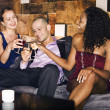 Man with two women sitting on couch in bar — Stock Photo