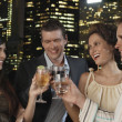 Couples toasting drinks against city skyline — Stock Photo