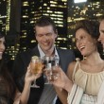 Couples toasting drinks against city skyline — Stock Photo