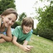 Boy and girl lying in grass — Stock Photo