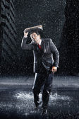 Businessman running through rain — Stock Photo