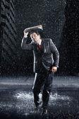 Businessman running through rain — Stock Photo