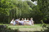 Family eating at table in garden — Stock Photo