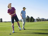 Golfers standing on course — Stockfoto