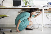 Businesswoman Adjusting Cables — Stock Photo