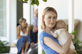 Mother holding baby on porch — Stock Photo