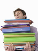 Office worker carrying heavy binders — Stock Photo