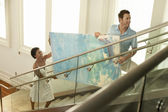 Couple moving modern painting up stairs — Stock Photo