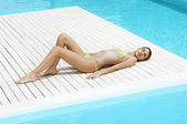 Woman Sunbathing by swimming pool — Stock Photo