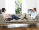 Couple reclining on couch — Stock Photo