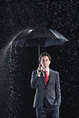Businessman standing under sturdy Umbrella — Stock Photo
