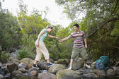 Couple Hiking Over Creek — Stock Photo