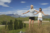 Women balancing on fence in field — Stockfoto