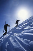 Skiers hiking to mountain summit — Stock Photo