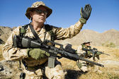 Soldier with weapon signaling — Stock Photo