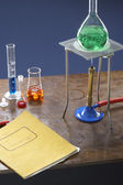 Bunsen burner, tripod, flask — Stock Photo