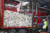 Man in vehicle loading stacks of recycled paper — Stock Photo