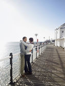 Couple embracing standing on pier — Stock Photo