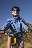 Woman on bicycle in field — Stock Photo