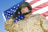 Soldier saluting in front of flag — Stock Photo