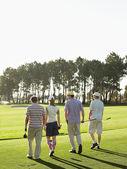 Golfers walking on golf course — Stock Photo