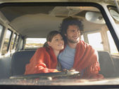 Couple wrapped in blanket in van — Stock Photo