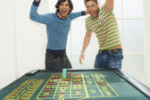 Men celebrating on roulette table — Stock Photo