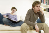 Man Watching Television with woman reading — Stock Photo