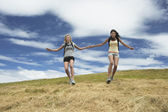 Two women holding hands skipping down hill — Stock Photo