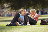 Couple reclining in park — Stok fotoğraf