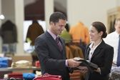 Salesperson assisting businessman in clothes store — Stock Photo