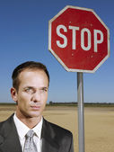 Man standing next to sign — Stock Photo
