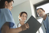 Physicians Reviewing Medical Chart — Stock Photo