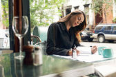Woman writing at sidewalk cafe — Stock Photo