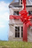 Model house gift-wrapped with red ribbon — Stock Photo
