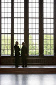 Men Conversing by tall windows — Stock Photo