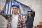 Сonstruction workers carrying ladder — Stock Photo