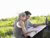 Man and woman looking at map — Stock Photo