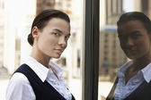 Woman standing reflected in window — Stock Photo