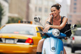 Woman using mobile phone on moped — Stock Photo