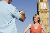 Husband taking photo of wife by Big Ben — Stock Photo