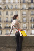 Woman posing with shopping bags on bridge — Stock Photo