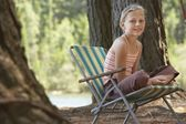 Girl Sitting on Deckchair in Forest — Stock Photo