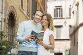 Couple holding guidebook — Stock Photo