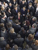 Business people surrounding woman looking up — Stock Photo